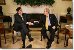 """President George W. Bush and President Alan Garcia of Peru share a light moment as they shake hands during a visit Monday, April 23, 2007, in the Oval Office. In the United States to promote free trade between the countries, the Peruvian leader said, """"It is important to show the world that a democracy, with investment, leads to development.""""  White House photo by Eric Draper"""