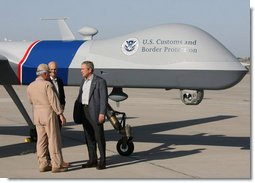 """Standing next to a Predator Drone, Maj. Gen. Mike Kostelnik speaks with President George W. Bush and Secretary Michael Chertoff of Homeland Security during their tour Monday, April 9, 2007, of the U.S.-Mexico border in Yuma, Ariz. Said the President, """"It's the most sophisticated technology we have, and it's down here on the border to help Border Patrol agents do their job.""""  White House photo by Eric Draper"""