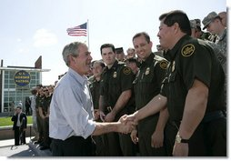 """President George W. Bush shakes hands with agents after speaking Monday, April 9, 2007, at the new Yuma Border Patrol Station on comprehensive immigration reform. Speaking in the Arizona border city, the President told his audience, """"We've got to resolve the status of millions of illegal immigrants already here in the country. So we're working closely with Republicans and Democrats to find a practical answer that lies between granting automatic citizenship to every illegal immigrant and deporting every illegal immigrant.""""  White House photo by Eric Draper"""
