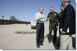 President George W. Bush emphasizes a point Monday, April 9, 2007, as he stands with Chief Border Patrol Agent Ron Colburn, center, and others during a tour of the U.S.-Mexico border in Yuma, Ariz. White House photo by Eric Draper