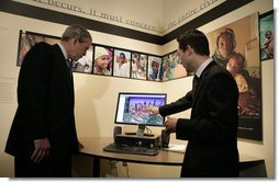 President George W. Bush watches a demonstration of Google Earth by Larry Swaider, Chief Information Officer for the U.S. Holocaust Memorial Museum, during his visit Wednesday, April 18, 2007. The President visited two exhibits and delivered remarks commemorating the Holocaust Days of Remembrance.  White House photo by Eric Draper