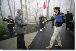 President George W. Bush reaches out to welcome Prime Minister Shinzo Abe to Camp David Friday, April 27, 2007. The leaders are expected to discuss their close cooperation in global affairs. White House photo by Eric Draper