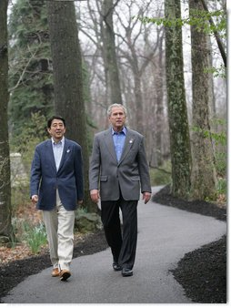 """President George W. Bush walks with Prime Minister Shinzo Abe during their meeting Friday, April 27, 2007, at Camp David. Said the President, """" We talked about the fact that our alliance -- and it is a global alliance -- is rooted in common values, especially our commitment to freedom and democracy."""" White House photo by Eric Draper"""