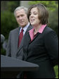 """President George W. Bush listens as Andrea Peterson, 2007 National Teacher of the Year, speaks during ceremonies Thursday, April 26, 2007, in the Rose Garden. Said the President, """"This is a special day for all who care deeply about education, because we fully understand that without a good teacher it's hard to achieve national goals and objectives."""" White House photo by Eric Draper"""