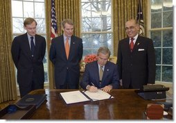 President George W. Bush signs the U.S.-Bahrain Free Trade Agreement in the Oval Office Wednesday, Jan. 11, 2006. Standing with the President are, from left: Deputy Secretary of State Robert Zoellick, U.S. Trade Representative Rob Portman, and Bahrain Ambassador Naser M. Al Belooshi.  White House photo by Paul Morse