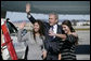 President George W. Bush waves to the friends and family of sisters Marni and Berni Barta of Los Angeles, Calif., after presenting them with the President's Volunteer Service Award, Wednesday, Jan. 30, 2008 in Los Angeles, for their founding of the not-for-profit program Kid Flicks. The Kid Flicks program collects and donates new and used DVDs to children's hospitals and pediatric centers across the U.S. White House photo by Eric Draper