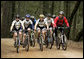 President George W. Bush rides with the Travis Air Force Base cycling team in the Los Posados State Forest, in Angwin, California, Saturday, April 22, 2006. White House photo by Eric Draper
