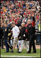 U.S. Army Sgt. Paul Brondhaver, left, U.S. Army Sgt. Mike McNaughton, center, and John Prazynski accompany President George W. Bush to the pitchers mound during the opening game between the Cincinnati Reds and the Chicago Cubs in Cincinnati, Ohio, Monday, April 3, 2006. The three men are involved with Impact Player Partners, an Ohio-based group that provides support for wounded soldiers and their families. White House photo by Eric Draper
