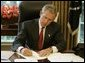 President George W. Bush signs executive orders and directives Friday, August 27, 2004, in the Oval Office, that strengthen the intelligence capabilities of the United States and take action consistent with certain recommendations of the 9/11 Commission. White House photo by Paul Morse