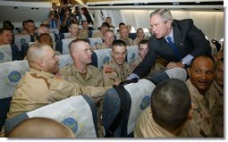 President George W. Bush greets members of two National Guard Units and an active Army unit headed to Iraq during a refueling stop in Bangor, Maine on September 23, 2004.  White House photo by Paul Morse