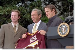 President George W. Bush accepts a team jersey from the NCAA Championship hockey team from the University of Minnesota on the South Lawn Tuesday, May 21. Also attending were University of Connecticut's women's basketball team, University of Maryland's men's basketball team, and University of Minnesota's women's hockey team. White House photo by Tina Hager.