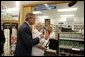 President George W. Bush helps senior Wanda Blackmore buy her prescriptions with her new drug discount card at the Hy-Vee pharmacy in Liberty, Mo., June 14, 2004. White House photo by Paul Morse