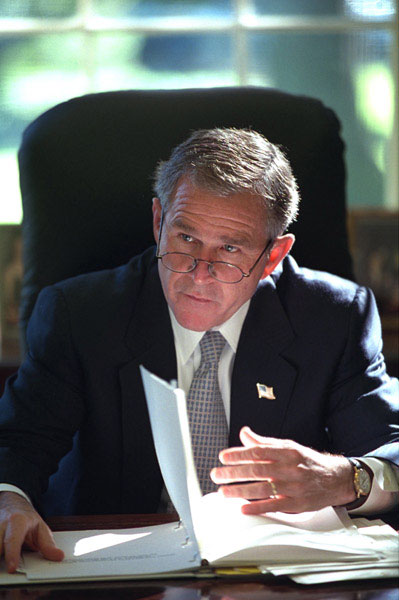 Working at his desk in the Oval Office, President George W. Bush prepares for his first meeting with the Homeland Security Team Oct. 29, 2001. White House photo by Eric Draper.