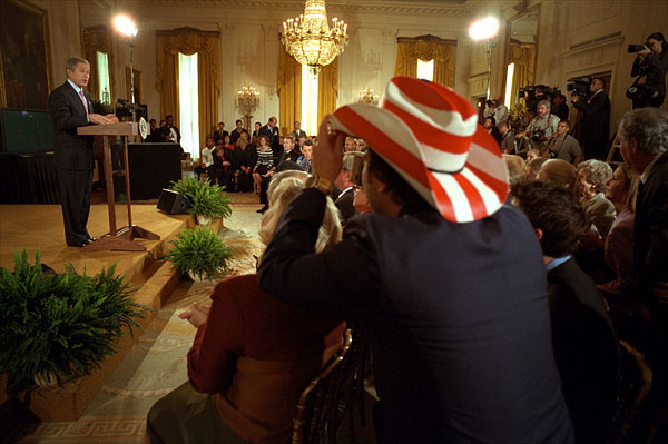 President George W. Bush addresses the audience in the East Room as actor Rob Schneider, decked out in a patriotic cowboy hat, takes a photograph Nov. 2. White House photo by Eric Draper.