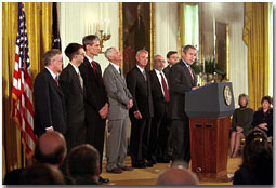 """""""Standing with me are seven of those who have been selected this year,"""" said President George W. Bush during a ceremony honoring the U. S. Nobel Laureates in the East Room Nov. 27. """"Among their achievements are path-breaking discoveries in physics, helpful insights in the workings of the market economies, and a new treatment for Parkinson's Disease."""" White House photo by Tina Hager."""