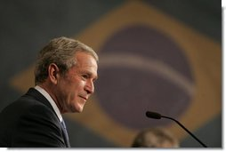 """President George W. Bush smiles as he listens to Brazil President Luiz Inacio Lula da Silva reply to a question Friday, March 9, 2007, during a joint press availability in Sao Paulo. Said President Lula, """"The memorandum of understanding on biofuels, which our ministers signed today, is a decisive step. Bringing together their efforts, the U.S. and Brazil can further push the democratization of energy and bring biofuels to all."""" White House photo by Paul Morse"""