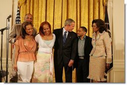 President George W. Bush celebrates Black Music Month Monday, June 6 2005, in the East Room of the White House. With him from left are artists: Reverend Donnie McClurkin; sisters Erica and Tina Campbell of Mary Mary; Smokie Norful, and Teresa Hairston, founder an publisher of Gospel Today and emcee of the event.  White House photo by Krisanne Johnson