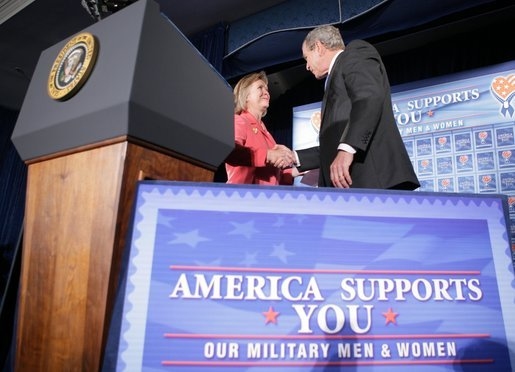 """President George W. Bush shakes the hand of Jonnie Nance, chairman of the Joint Armed Forces Officers' Wives Luncheon, after being introduced by her Tuesday, Oct. 25, 2005, at the Bolling Air Force Base Officers' Club in Washington, D.C. The President told the audience that he understood it was a trying time for military spouses, adding: """"By standing behind those who serve, you're serving, as well."""" White House photo by Paul Morse"""