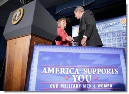"President George W. Bush shakes the hand of Jonnie Nance, chairman of the Joint Armed Forces Officers' Wives Luncheon, after being introduced by her Tuesday, Oct. 25, 2005, at the Bolling Air Force Base Officers' Club in Washington, D.C. The President told the audience that he understood it was a trying time for military spouses, adding: ""By standing behind those who serve, you're serving, as well.""  White House photo by Paul Morse"
