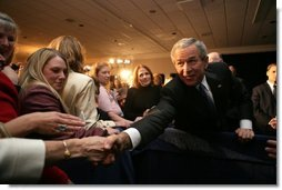 President George W. Bush reaches out for the hand of well-wisher after speaking Tuesday, Oct. 25, 2005, to the Joint Armed Forces Officers' Wives Luncheon at the Bolling Air Force Base Officer's Club in Washington, D.C.  White House photo by Paul Morse