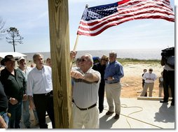 President George W. Bush watches as homeowner Jerry Akins places a flag outside his home Wednesday, March 8, 2006 in Gautier, Miss., on the site where the Akins family is rebuilding their home destroyed by Hurricane Katrina. White House photo by Eric Draper