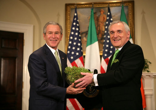 President George W. Bush is presented a bowl of shamrocks by Prime Minister Bertie Ahern of Ireland, during a ceremony Friday, St. Patrick's Day 2006, in the Roosevelt Room of the White House. White House photo by Kimberlee Hewitt