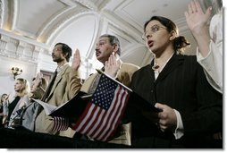 Naturalization ceremony participants raise their hands and hold American flags as they are sworn-in as new U.S. citizens Monday, March 27, 2006, during the Naturalization Ceremony at the Daughters of the American Revolution Administration Building in Washington. President George W.Bush addressed the audience, saying that each generation of immigrants brings a renewal to our national character and adds vitality to our culture. White House photo by Eric Draper