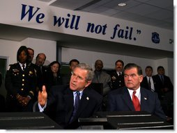 President George W. Bush answers questions from the press during a tour of the District of Columbia's Metropolitan Police Department Synchronized Operations Center, Tuesday, Nov. 12. Homeland Security Advisor Tom Ridge, right, also participated in the tour.   White House photo by Paul Morse