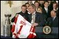Receiving a jersey from team captain Steve Yzerman, President George W. Bush welcomes the Detroit Red Wings, winners of the NHL 2002 Stanley Cup Championship, to the East Room of the White House Friday, Nov. 8. White House photo by Paul Morse.