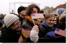 "Waiting for President Bush and President Adamkus, a crowd member plays with the American and Lithuanian flag at the Rotuse Square in Vilnius, Lithuania, Nov. 23. ""You (the Lithuanian people) have known cruel oppression and withstood it. You were held captive by an empire and you outlived it. And because you have paid its cost you know the value of human freedom,"" said President Bush in his remarks. ""Lithuania today is true to its best traditions of democracy and tolerance and religious liberty, and you have earned the respect of my nation and all nations.""  White House photo by Paul Morse"