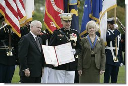 Outgoing Joint Chiefs of Staff Chairman U.S. Marine General Peter Pace, joined by his wife, Lynne Pace, right, receives his official certificate of retirement from the U.S. Marine Corps from U.S. Secretary of Defense Robert Gates, during the Armed Forces farewell tribute in honor of General Pace and the Armed Forces hail in honor of the new Joint Chiefs of Staff Chairman Navy Admiral Michael Mullen, Monday, October 1, 2007 at Fort Myer, Virginia. White House photo by Eric Draper