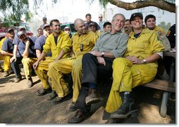 """President George W. Bush visits a base camp Thursday, Oct. 25, 2007, for First Responders battling the Southern California wildfires. """"I'm telling you, there's a lot of folks that live up in these hills that have their houses because of you,"""" the President told the fire fighters. """". They're not in a position to thank you -- but we are. And so we thank you for helping save lives and save property."""" White House photo by Eric Draper"""