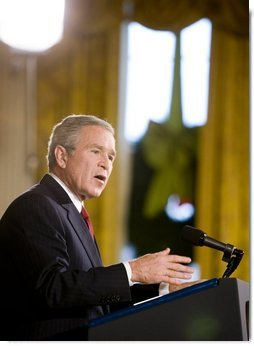 """President George W. Bush addresses the media during a press conference Monday, Dec. 19, 2005, in the East Room of the White House. Before responding to reporters' questioning, the President, speaking on Iraq, told the gathering, """". This election does not mean the end of violence, but it is the beginning of something new: A constitutional democracy at the heart of the Middle East.""""  White House photo by Paul Morse"""