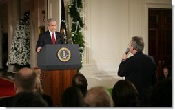 """President George W. Bush listens as Terrence Hunt of The Associated Press delivers a question Monday, Dec. 19, 2005, during the President's press conference in the East Room of the White House. In response to Mr. Hunt's question, the President responded, """"We're at war, and we must protect America's secrets.""""  White House photo by Paul Morse"""
