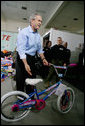 """President George W. Bush helps guide a donated bicycle to a toy distribition vehicle, Monday, Dec. 19, 2005, at the """"Toys for Tots"""" collection center at the Naval District Washington Anacostia Annex in Washington, D.C. White House photo by Kimberlee Hewitt"""