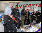 """President George W. Bush helps U.S. Marines sort through a stack of toys Monday, Dec. 19, 2005 at the """"Toys for Tots"""" collection center at the Naval District Washington Anacostia Annex in Washington, D.C. White House photo by Kimberlee Hewitt"""