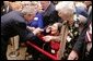 President George W. Bush bends to meet Jean Tessier of Tyson's Corner, Va., during his visit Tuesday, Dec. 13, 2005, to the Medicare Prescription Drug Educational and Enrollment Event at the Greenspring Village Retirement Community in Springfield, Va. White House photo by Paul Morse