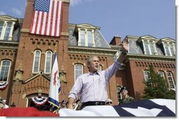 """President George W. Bush waves to the estimated 3,000 people in attendance at an Independence Day celebration Monday, July 4, 2005, at West Virginia University in Morgantown. Said the President, """"The history we celebrate today is a testament to the power of freedom to lift up a whole nation.""""  White House photo by Krisanne Johnson"""