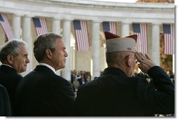 """President George W. Bush stands with Secretary of Veterans Affairs Anthony Principi, left, and Mr. Gene Overstreet, President of the Non-Commissioned Officers Association, during the Veterans Day ceremonies at Arlington National Cemetery Nov. 11, 2004. """"We honor every soldier, sailor, airman, Marine and Coastguardsman who gave some of the best years of their lives to the service of the United States and stood ready to give life, itself, on our behalf,"""" said the President in his remarks. White House photo by Paul Morse"""