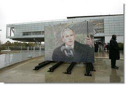 """As pictured on an outdoor video screen, President George W. Bush addresses attendees during the dedication of former President Bill Clinton's Presidential Center and Park in Little Rock, Ark., Nov. 18, 2004. """"He was a tireless champion of peace in the Middle East. He used American power in the Balkans to confront aggression and halt ethnic cleansing. And in all his actions and decisions, the American people sensed a deep empathy for the poor and the powerless,"""" said President Bush.  White House photo by Eric Draper"""