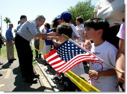 President George W. Bush greets a crowd during an unscheduled stop at a Laredo, Texas, elementary school after visiting the Laredo Border Patrol Sector Headquarters, Tuesday, June 6, 2006. White House photo by Eric Draper