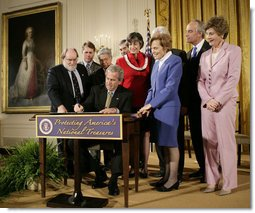 President George W. Bush signs a proclamation to create the Northwestern Hawaiian Islands Marine National Monument at a ceremony Wednesday, June 15, 2006, in the East Room of the White House. The proclamation will bring nearly 140,000 square miles of the Northwestern Hawaiian Island Coral Reef Ecosystem under the nation's highest form of marine environmental protection. Mrs. Laura Bush joined the President and distinguished guests on stage, from left to right, U.S. Rep. Neil Abercrombie, D-Hawaii; U.S. Rep. Ed Case, D-Hawaii; U.S. Sen. Daniel Akaka, D-Hawaii; U.S. Commerce Secretary Carlos Gutierrez; Hawaii Gov. Linda Lingle; documentary filmmaker Jean-Michel Cousteau; marine biologist Sylvia Earle and U.S. Interior Secretary Dirk Kempthorne. White House photo by Eric Draper