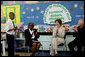 """Mrs. Laura Bush joins Our Lady of Perpetual Help School principal Charlene Hursey, left, and Cardinal Theodore McCarrick, Archbishop of Washington, D.C., in applauding student Marquette Lewis, 11, after his reading of the poem """"Coming of Age,"""" Monday, June 5, 2006. Mrs. Bush visited the school to announce a Laura Bush Foundation for America's Libraries grant to Our Lady of Perpetual Help School. White House photo by Shealah Craighead"""