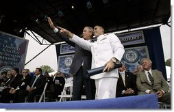 President George W. Bush waves to the audience with a recent graduate during the graduation ceremony at the United States Merchant Marine Academy at Kings Point, New York, Monday, June 19, 2006. White House photo by Kimberlee Hewitt