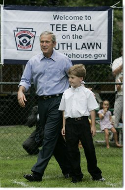 President George W. Bush joins Zane Ellingwood, the First Ball Presenter, on the South Lawn of the White House at the opening game of the 2006 Tee Ball season, Friday, June 23, 2006, between the McGuire Air Force Base Little League Yankees and the Dolcom Little League Indians of the Naval Submarine Base from Groton, Ct.  White House photo by Paul Morse