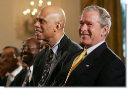 President George W. Bush is joined by basketball Hall of Famer Kareem Abdul Jabbar in the East Room of the White House Monday, June 26, 2006, as they listen to performer Patti Austin at the Black Music Month celebration focusing on the music of the Gulf Coast: Blues, Jazz and Soul.  White House photo by Eric Draper