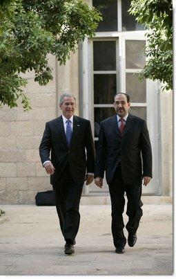 "President George W. Bush walks with Prime Minister Nouri al-Maliki Tuesday, June 13, 2006, at the U.S. Embassy in Baghdad, Iraq. During his unannounced trip to Iraq, President Bush thanked the Prime Minister, telling him, ""I'm convinced you will succeed, and so will the world.""  White House photo by Eric Draper"
