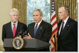 """Standing with former Presidents Bill Clinton and George H. W. Bush, President George W. Bush discusses the plans to help people affected by Hurricane Katrina in the Oval Office Sept. 1, 2005. """"We're working hard to repair the breaches in the levees. Federal, state, and local agencies are also cooperating to sustain life,"""" President Bush. """"That means getting food and water to those who are stranded. Medical personnel and local officials are helping hospital patients and people gathered in the Superdome to evacuate.""""  White House photo by Paul Morse"""
