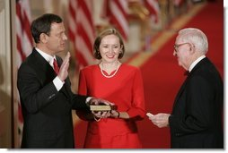 Judge John G. Roberts is sworn-in as the 17th Chief Justice of the United States by Associated Supreme Court Justice John Paul Stevens, Thursday, Sept. 29, 2005 in the East Room of the White House in Washington. Judge Roberts' wife Jane is seen holding the Bible.  White House photo by Paul Morse