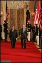 """President George W. Bush and President Jalal Talabani of Iraq walk to the East Room of the White House Tuesday, Sept. 13, 2005, for a joint press availability. The President called Iraq """"America's ally in the war against terrorism,"""" and added, """"freedom will win in Iraq."""" White House photo by Shealah Craighead"""